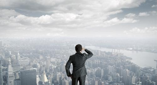 A businessman looks over a cityscape.